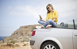 Woman Sitting on Car Looking at Her Phone